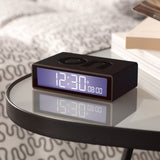 The FLIP alarm clock featured in black, resting atop a glass side table.