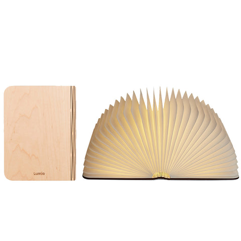 Small book with pages open like an accordion, light illuminates from within. Next to the open book light, a closed maple Lumio stands upright and faces forward.
