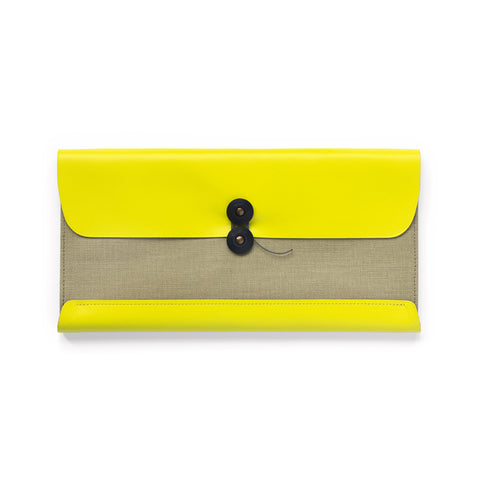 Leather and pressed cotton canvas long rectangular wallet with black string closure. Neon yellow leather covers the back and borders of this wallet.