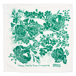 "One unfolded napkin American Folk Art Dinner Napkin in green, showing the full floral illustration comprised of lillies, roses, ivy and other foliage. The green color has a hint of blue. Below the illustration is cursive text that says ""American folk Art Series arranged by"" and to the right of that ""Marguerita Mergentime"" in all caps on a wavy line."