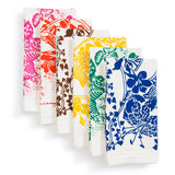 Cascade stack of six folded napkins, each with a different vibrantly colored floral graphic printed on   white, flour-sack like fabric. Colors from left to right are: magenta, red orange, brown, yellow, green, blue.
