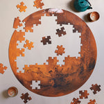 Circular, half put-together puzzle that is a photograph of Mars.