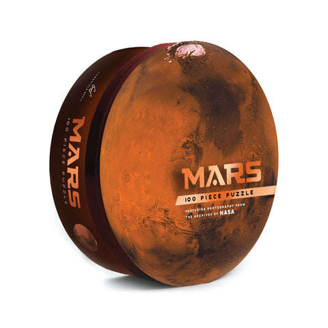 Red-brown circular puzzle box, standing upright. The top of the lid is a full-bleed photo of Mars. Off-center title text is printed in a copper-toned metallic ink.