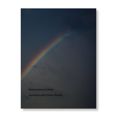 A book featuring a rainbow on its cover against a dark backdrop. There is black text printed on the bottom left corner of the book cover.