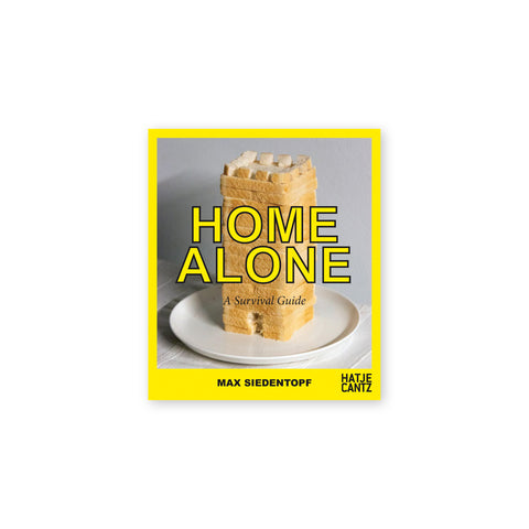A photo of a loaf of bread stacked vertically on a white plate and featuring tiny cut out cubes placed on the top slice. The photo is surrounded by a bright yellow frame. The title of the book is also a bright yellow and is printed at the center of the photo. The author's name is printed in bold black text at the bottom right corner of the book.