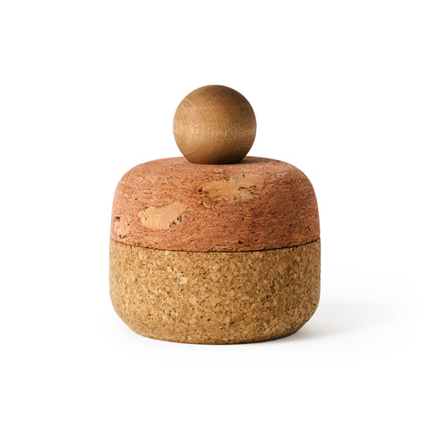 Squircle shaped container with equally proportioned pink cork lid and brown cork bottom with a sphere-shaped maple wood handle, shot on a white background.