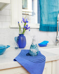 Island Rain Gel Hand Wash bottle sitting on a marble kitchen counter, with a blue towel underneath the bottle, surrounded by blue and indigo accent accessories.