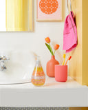 Orange Slice Gel Hand Wash bottle sitting on a white bathroom counter, surrounded by orange and pink accent accessories, with a porcelain sink to the left and a yellow wall to the right.