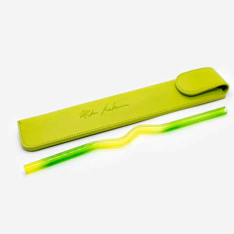 The Green & Yellow Suck It Up Glass Straw, with gradating yellow and green stripes, shaped in a zig zag in the middle. The straw is lying next to a long chartreuse pouch featuring Misha Kahn's signature.