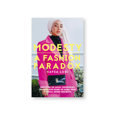"Book cover featuring a photograph of an accessorized woman in a pink power suit, wearing hijab. Yellow text overlaid reads: ""Modesty A Fashion Paradox"""