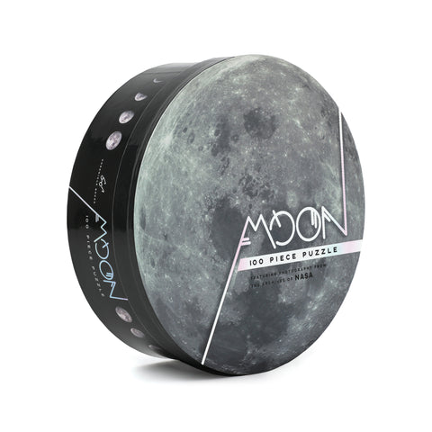 Black circular puzzle box, standing upright. The top of the lid is a full-bleed photo of the moon. Off-center title text is printed in a silver metallic ink.