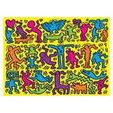 One side of the Keith Haring 2-Sided Puzzle features an all-over pattern of colorful figures on a yellow background.