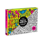 "Angle view of a box featuring two all-over Keith Haring drawings, one colorful, the other black-and-white, split from corner to corner. White text on a black circle in the center reads ""2-in-1 Keith Haring Double Sided Puzzle"""