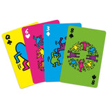 A hand of four playing cards, each is a different color and features a different Keith Haring drawing.