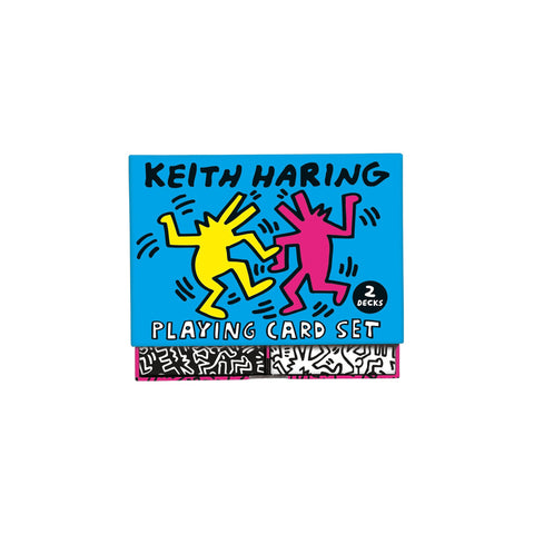 "Slightly opened box of two decks of cards, one black with white drawings, the other white with black drawings. The box features a Keith Haring drawing on a vibrant blue background, text above and below reads ""Keith Haring Playing Card Set""."