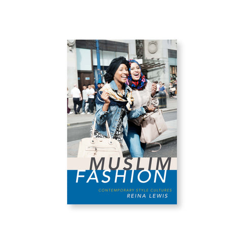 Muslim Fashion book cover featuring a photograph of two women wearing denim and carrying large purses, one wearing a turban and one wearing a hijab, laughing as they crossing a street. Title in a blue band across the bottom of the cover.