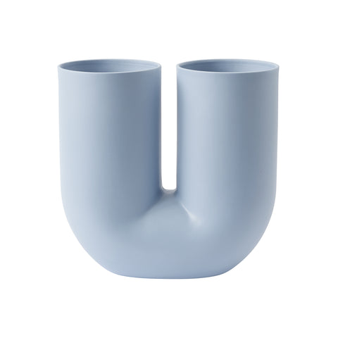 "A light blue tubular vase in the shape of a ""U"" with two separate openings."