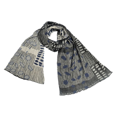 A scarf featuring a crinkled texture fabric with scattered bean designs woven throughout. Colors included in the scarf are shades of black, off-white, and blue.