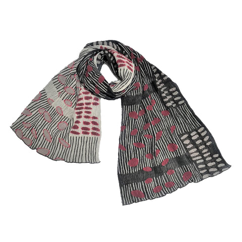 A scarf featuring a crinkled texture fabric with scattered bean designs woven throughout. Colors included in the scarf are shades of black, off-white, and red.