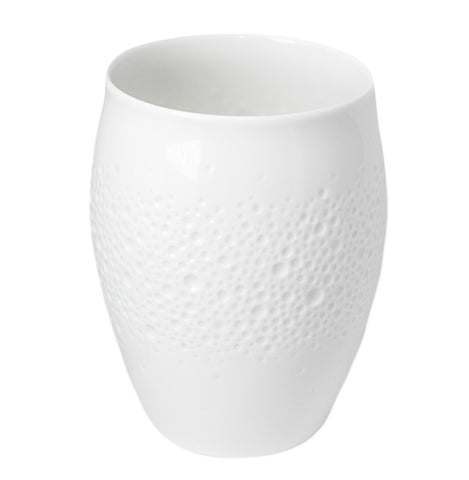 A bright white, glazed porcelain cup, egg-shaped, with a broad middle-band of shallow, circular indentations inspired by the sensuous appearance of sun-bleached coral.