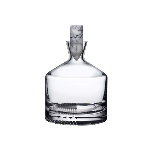 The Alba Whiskey Decanter featuring a slender neck that tapers towards the brim and a wide lower body. The base of the decanter features a hand engraved, deconstructed tartan pattern. There is a circular white marble stopper inserted at the neck.