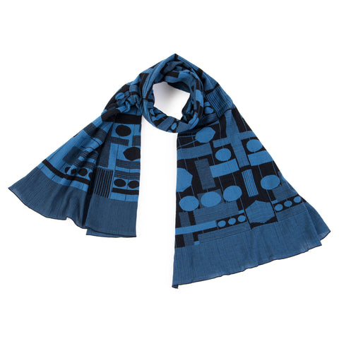 Black and blue scarf with an all-over geometric pattern of circles, rectangles, stripes and lines. The scarf is looped with a wide border made up of thin stripes at either end.