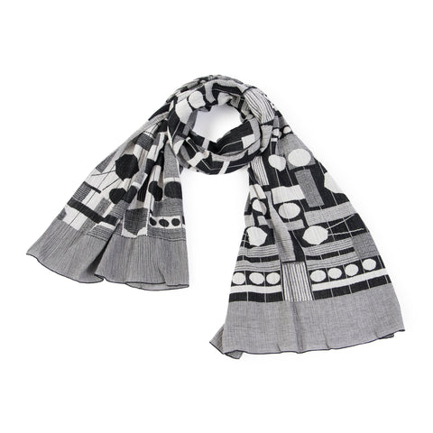 Black, white, and gray scarf with an all-over geometric pattern of circles, rectangles, stripes and lines. The scarf is looped and has a wide border made up of thin stripes at either end.