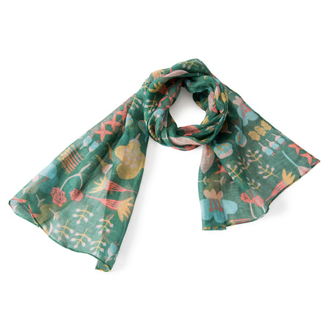 Green scarf with an all-over pattern of different pink, red, yellow, and light blue flowers in a youthful illustration style. The scarf is looped with the ends splayed.