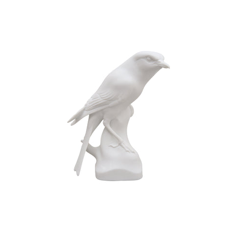 A realistic shrike in matte, white bisque porcelain, with an alert expression, closed, curved beak, forked tail and folded wings, perched on vertical branch-like base.