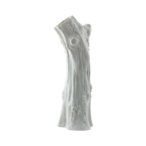 A detailed glazed, white porcelain vase in the shape of a tall, erect tree trunk with realistic bark, knots and patches of lichen.