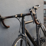 Lifestyle image of a black bicycle propped against a gray textured wall showing leather wrapped handlebars, breaks and cables, a water bottle holder and brass accessories, including the curved brass Oi bicycle bell.