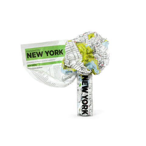 A crumpled piece of fabric squeezing into a small clear package labeled New York. The crumpled fabric appears to have green space and city streets and a key.