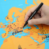A hand reaches onto a detail of the map with a pen to draw pins and notes on it.