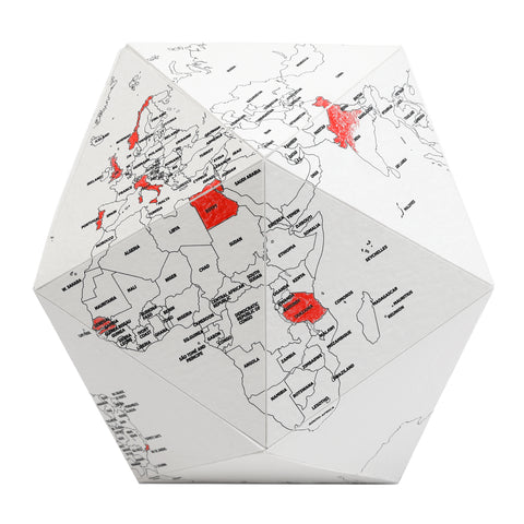 A 3D model of a globe made of white textured paper. Various countries on the globe are filled in with red color pencil.