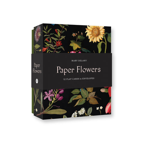 Card and envelopes box set featuring a series of floral illustrations placed on a black backdrop. There is a black belly band around the box. The name of the card set is printed in white font on the front of the belly band.
