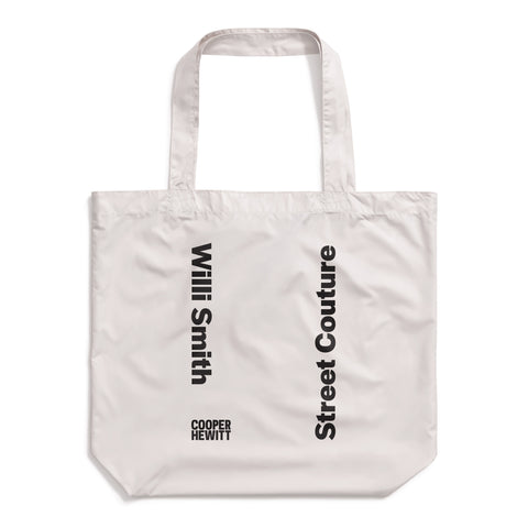"Light gray tote bag made of a slightly shiny material, with vertical bold, black text reading ""Willi Smith"" facing opposite ""Street Couture"". Cooper Hewitt logo at bottom left."