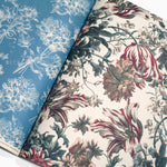 Interior pages of wrapping paper book showing a floral interior page in blue and white and another in creams, reds, and black.