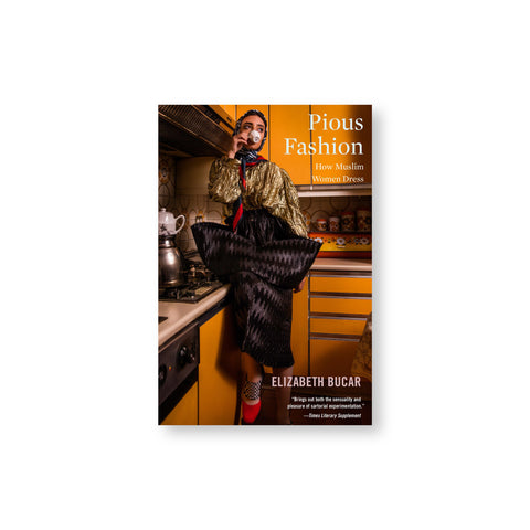 Pious Fashion book cover featuring a moody editorial photograph of a woman wearing luxurious textiles and head scarf, sipping a cup of tea while sitting on a counter in an amber kitchen. Minimal cover title at the upper right of the cover.