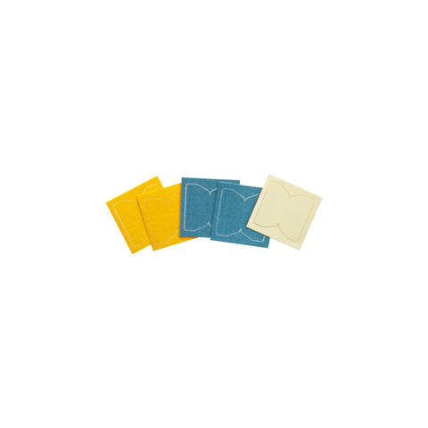 Five pressed cotton fabric tabs in yellow, blue, and white