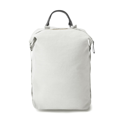 A light grey medium sized backpack with black leather top handle.