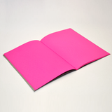 A notebook opened to reveal the bight pink black pages inside.