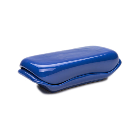 Image featuring a saturated blue colored dish with rounded edges and a matching lid on top. The butter dish is placed in the center of the image at an angle slightly towards the right, creating a depth in space.