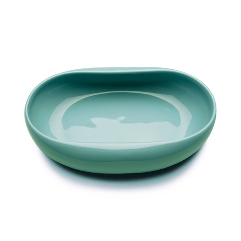 Oval-based ceramic dish with a curvy silhouette of two long sides softly curved inwards. The exterior and interior of the dish are evenly glazed with a glossy finish of subtle turquoise pigment.