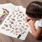 Child on a wooden floor coloring in the bug illustrations on the Insects Color-In Shirt with a marker.