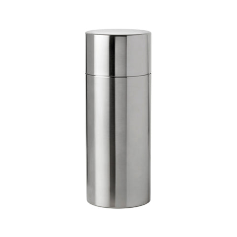 Cylindrical, steel cocktail shaker made of two separate pieces, the body longer than the top. Sides are straight and top and bottom are flat.