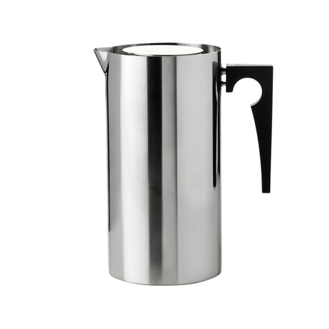 Cylindrical steel vessel with a small spout at the top edge, flat top with space around the edge, and a black handle. Handle's outside edge is a right angle and the inside edge is a curve with a circle cut into it.