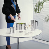 In a white space, a steel salad bowl, salt and pepper mills, jug, stacked coasters, and two martinis in glasses sit on a white table with a narrow steel stem. A person wearing a flashy black and blue outfit, holds tongs and tosses a salad in the bowl. One wall behind features a slatted window shade. Palm leaves are cut off at right.