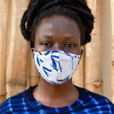 Model wearing a face mask made of a pale blue fabric printed with indigo floret silhouettes, and a navy tie dyed shirt.