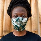 Model wearing a face mask made of a deep green fabric printed with abstract green shapes, and a dark shirt.