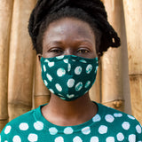 Model wearing a face mask made of a deep green fabric printed with white polka dots, and a matching shirt.